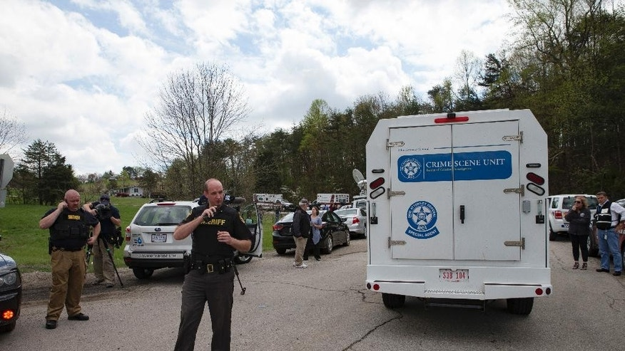 Authorities allow crime scene investigation vehicles to pass a perimeter checkpoint near a crime scene, Friday, April 22, 2016, in Pike County, Ohio. Shootings with multiple fatalities were reported along a road in rural Ohio on Friday morning, but details on the number of deaths and the whereabouts of the suspect or suspects weren't immediately clear. The attorney general's office said a dozen Bureau of Criminal Investigation agents had been called to Pike County, an economically struggling area in the Appalachian region some 80 miles east of Cincinnati. (AP Photo/John Minchillo)
