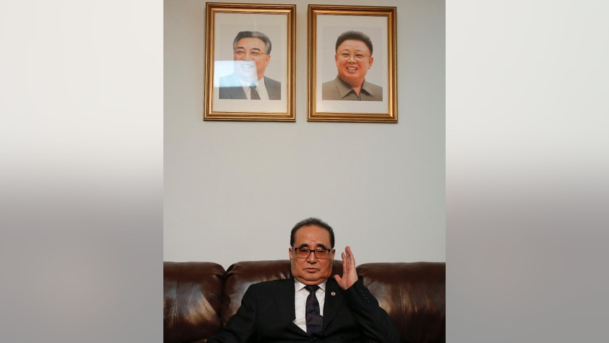 Seated under portraits of former North Korean Leaders Kim Il Sung, left, and Kim Jong Il, North Korea's Foreign Minister Ri Su Yong answers questions during an interview, Saturday, April 23, 2016, at the country's Permanent Mission to the United Nations in New York. (AP Photo/Julie Jacobson)