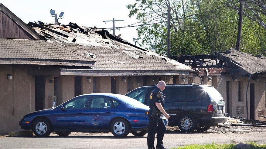 A Topeka police officer looks back at the scene Sunday, April 24, 2016, at the Country Club Motel, in Topeka, Kan., where two deputy U.S. marshals and one FBI agent suffered gunshot wounds as they tried to arrest a robbery suspect late Saturday night. (Thad Allton/The Topeka Capital-Journal via AP) MANDATORY CREDIT