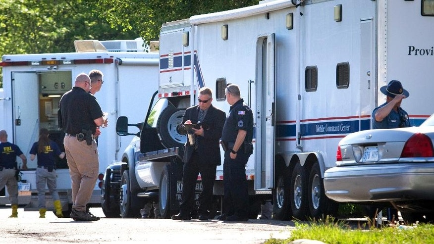 Authorities continue working the scene Sunday, April 24, 2016, at the Country Club Motel, in Topeka, Kan., where two deputy U.S. marshals and one FBI agent suffered gunshot wounds as they tried to arrest a robbery suspect late Saturday night. (Thad Allton/The Topeka Capital-Journal via AP) MANDATORY CREDIT