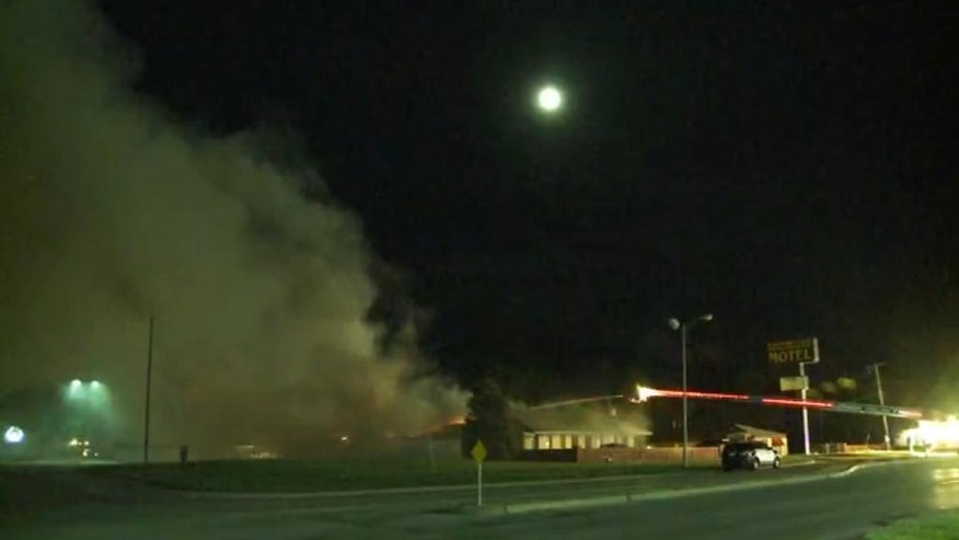 Smoke rises from a fire at a motel following a Saturday, April 23, 2016, shootout in Topeka, Kan. Authorities say gunshots were exchanged with federal agents, and firefighters worked to douse the fire. (WIBW via AP) MANDATORY CREDIT