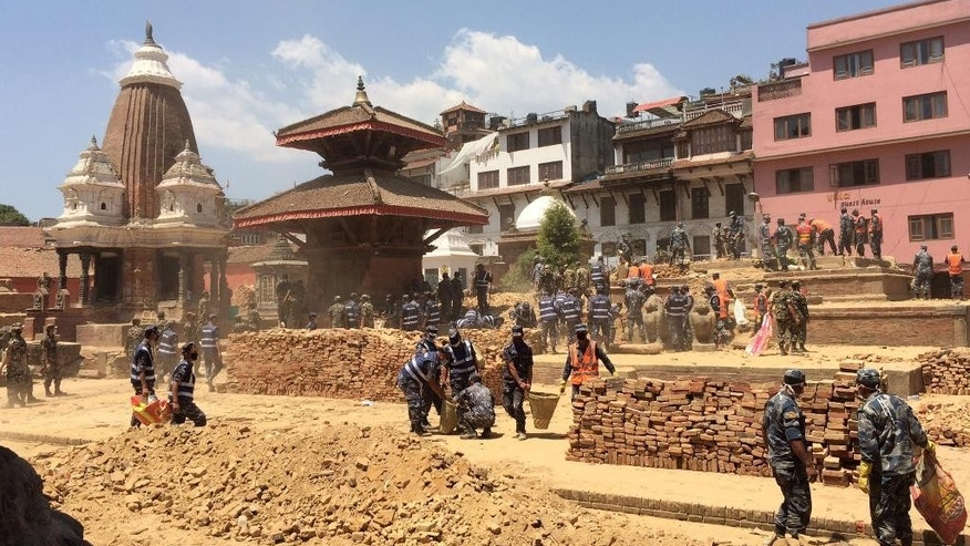 In this May 3, 2015 photo provided by the World Monuments Fund, soldiers help rescue materials from the Char Narayen Temple that was destroyed in a massive earthquake, in Patan, Nepal. One year to the day after the earthquake claimed 9,000 lives, the New York-based preservation group, the World Monuments Fund, has announced grants totaling $1 million for five historic sites, including the 16th century temple that will be 90 percent rebuilt with salvaged pieces and seismically retrofitted. (Rohit Ranjitkar/Kathmandu Valley Preservation Trust & World Monuments Fund via AP)