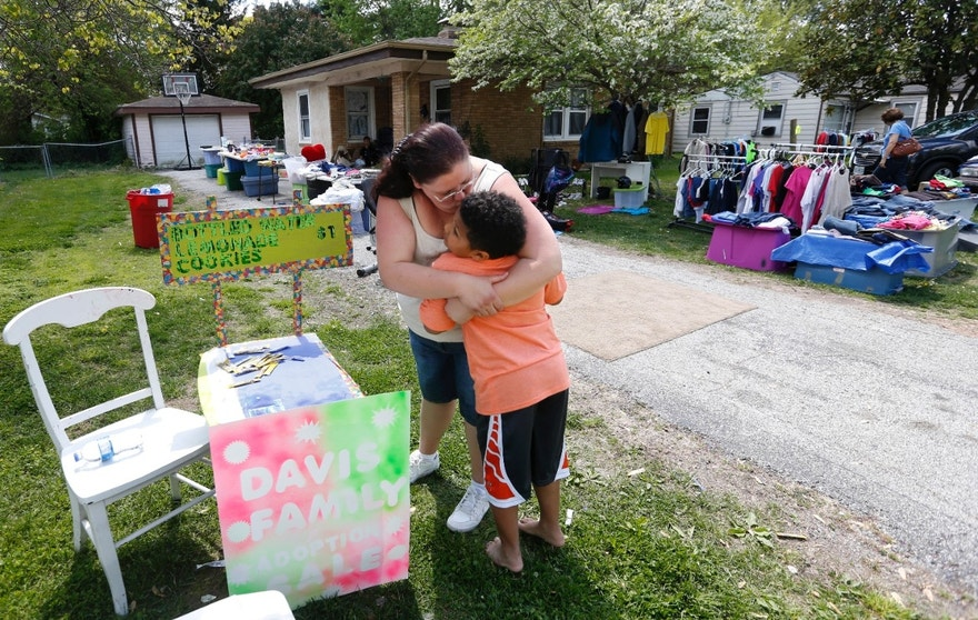 In this April 22, 2016 photo, Donnie Davis gives Tristan Jacobson a kiss outside their home in Springfield, Mo. Tristan has been living with with Donnie and Jimmy Davis, who have been Tristan's kinship guardians. They have been holding a yard sale and set up a lemonade stand to raise money for his adoption. (Andrew Jansen/The Springfield News-Leader via AP) NO SALES; MANDATORY CREDIT