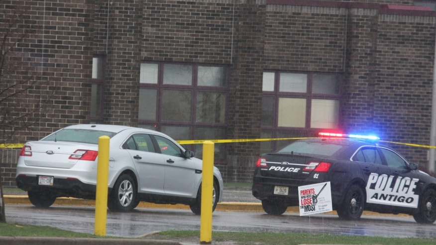 Two Antigo police department vehicles sit outside the front entrance of Antigo High School.