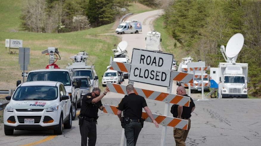 FILE - In this Friday, April 22, 2016 file photo, authorities set up road blocks at the intersection of Union Hill Road and Route 32 at the perimeter of a crime scene, in Pike County, Ohio. As the investigation into the killings of eight family members in rural Ohio enters its fifth day, more details are being released. Pike County Prosecutor Rob Junk told The Columbus Dispatch Monday, April 25, 2016, that the marijuana operations discovered at three of the four crime scenes included a grow-house sheltering hundreds of plants.  (AP Photo/John Minchillo, File)