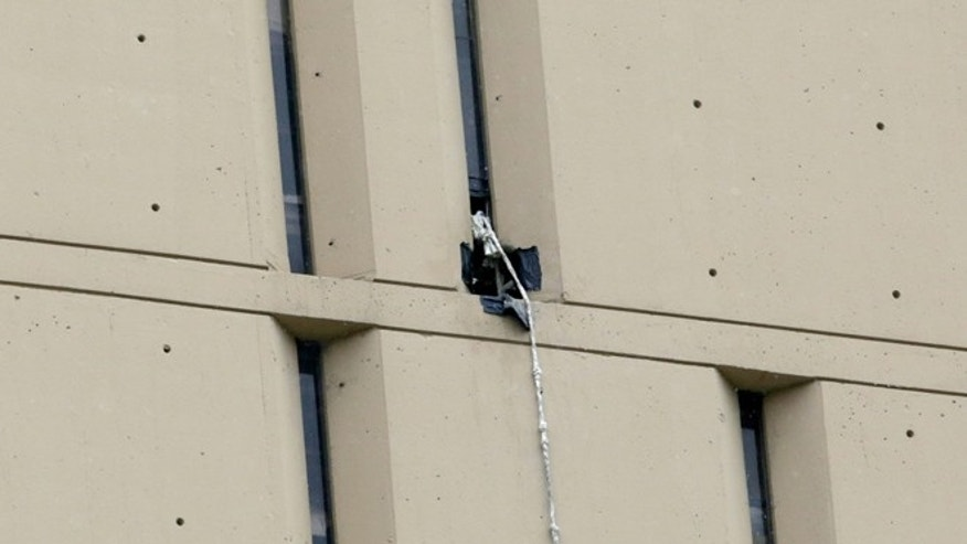 In the Dec. 18, 2012 file photo, a rope that two bank robbers used to escape from Chicago's Metropolitan Correctional Center, dangles from a window on the back side of the prison.