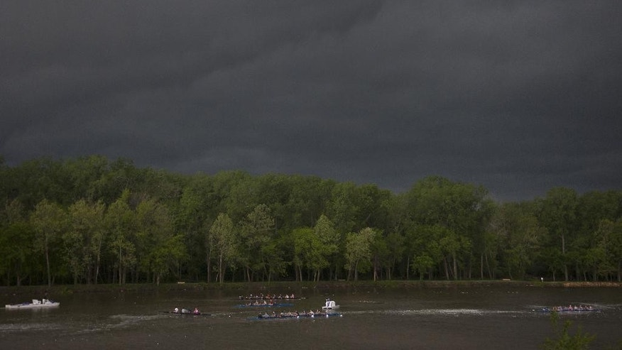 The Kansas University rowing team practices on the Kansas River under threatening clouds as a storm front moves over Lawrence, Kan. early Tuesday morning, April 26, 2016. (Mike Yoder/Lawrence Journal-World via AP)