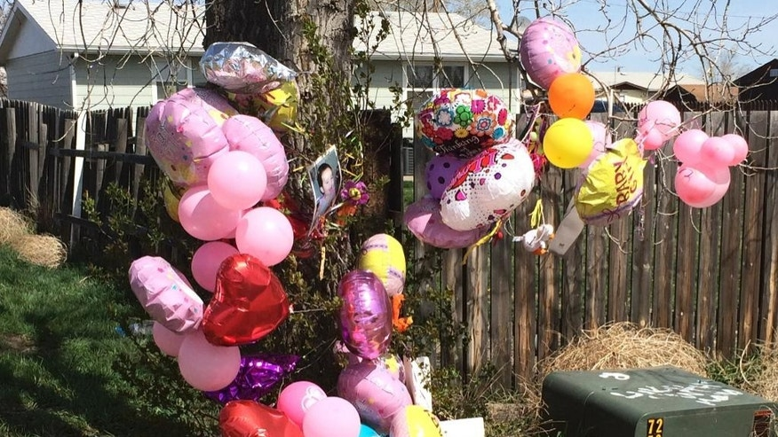 A memorial is placed in front of the house for 1-year-old Kenzley Olson on Friday, April 22, 2016, in Poplar, Mont. A federal investigator says a woman beat to death the girl on a Montana Indian reservation and threw the baby's body into a dumpster. Janelle Red Dog appeared in Fort Peck Tribal Court on Friday in the death of Olson after she reportedly confessed and drew a map of where the body was located. (AP Photo/Richard Peterson)