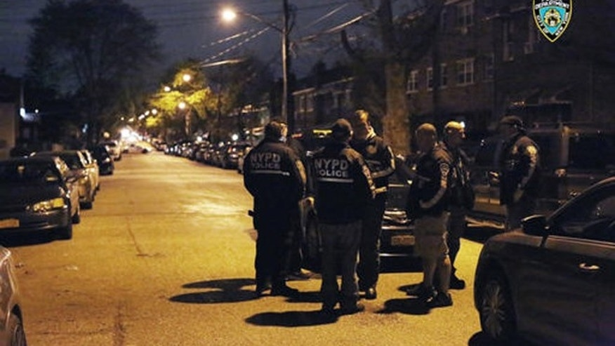 In this photo provided by the New York City Police Department, officers gather at a location in the Bronx borough of New York during a takedown of two rival drug gangs in the early hours of Wednesday, April 27, 2016.