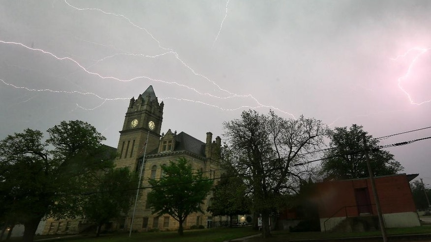 Lightning illuminates the sky over the Marion County Courthouse in Marion, Kan., Tuesday, April 26, 2016. Thunderstorms bearing hail as big as grapefruit and winds approaching hurricane strength lashed portions of the Great Plains on Tuesday. (AP Photo/Orlin Wagner)