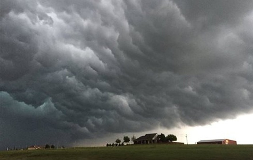 Storm clouds appear over a home near Meers, Okla., Tuesday, April 26, 2016. Strong thunderstorms capable of dropping grapefruit-sized hail and producing a few intense tornadoes popped up across the central U.S. on Tuesday after forecasters warned that millions of people faced a significant danger. (Robert MacDonald via AP) MANDATORY CREDIT