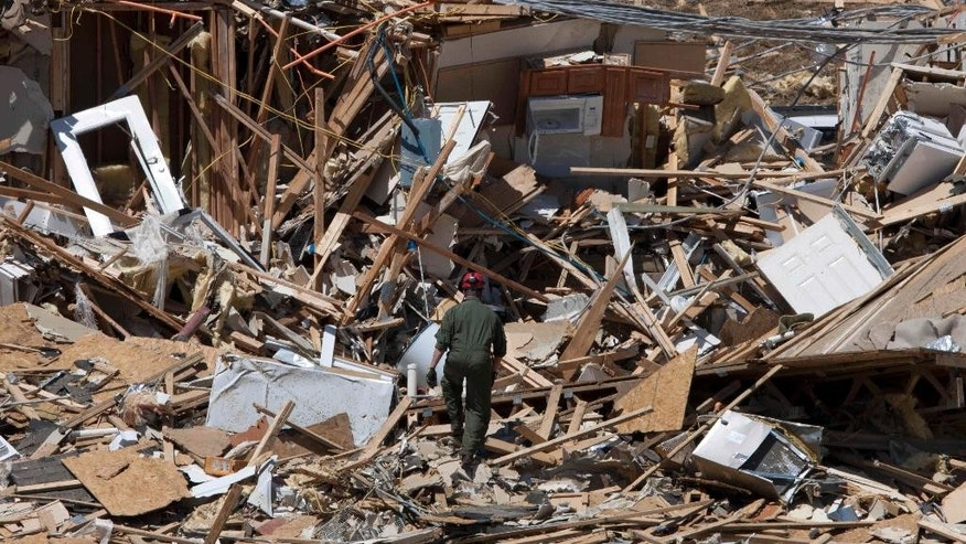 FILE - In this file photo taken May 4, 2011, Tuscaloosa Fire Lt. Brian Phillips climbs a pile of rubble in search of survivors or bodies at an apartment building in Tuscaloosa, Ala. On April 27, 2011, a series of tornadoes killed hundreds of people, injured thousands and reduced countless buildings to rubble across a swath of the U.S. Casualties were reported in Mississippi, Georgia, Tennessee, Virginia and Alabama - which was the hardest hit, with a death toll of more than 250 in that state alone. (AP Photo/Dave Martin, File)