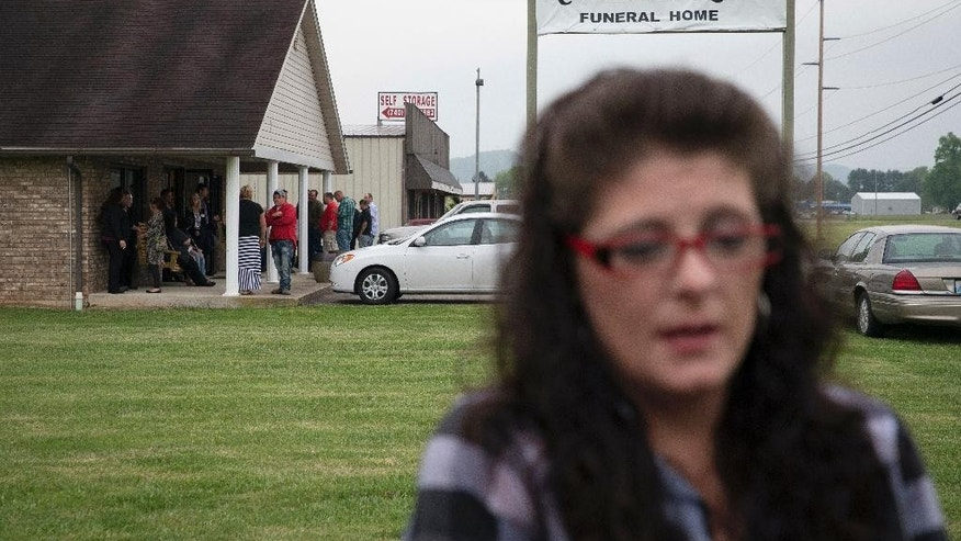 Lisa Wallace, former sister-in-law of Gary Rhoden, speaks to the media outside of his wake at the Crockett L. Reed Funeral Home, Wednesday, April 27, 2016, in South Shore, Ky. Multiple people, including Rhoden, were found dead Friday at several properties near Piketon, Ohio. Investigators have interviewed more than 50 people in the case but have made no arrests. (AP Photo/John Minchillo)