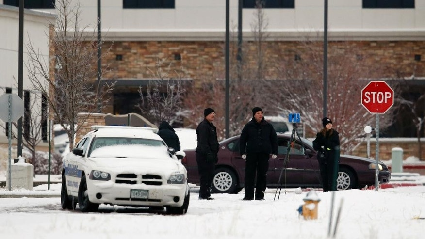 In this Nov. 28, 2015 file photo, police investigators work near a Planned Parenthood clinic in Colorado Springs, Colo., after a deadly shooting Friday. The man who acknowledges killing three people at the Colorado Planned Parenthood clinic will return to court for a discussion of his mental health. The hearing on Thursday, April 28, 2016, will focus on whether 57-year-old Robert Dear is competent to continue with his criminal case. (AP Photo/David Zalubowski)