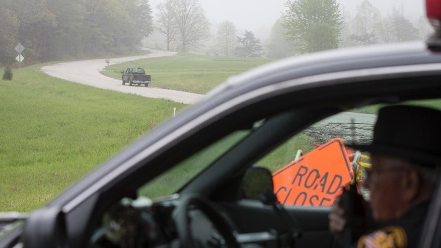 Leonard Manley, left, father and grandfather of several murder victims, drives up Union Hill Road away from a roadblock at the outer perimeter of a crime scene, Wednesday, April 27, 2016, near Piketon, Ohio. Several people were found dead Friday at multiple properties near Piketon. (AP Photo/John Minchillo)