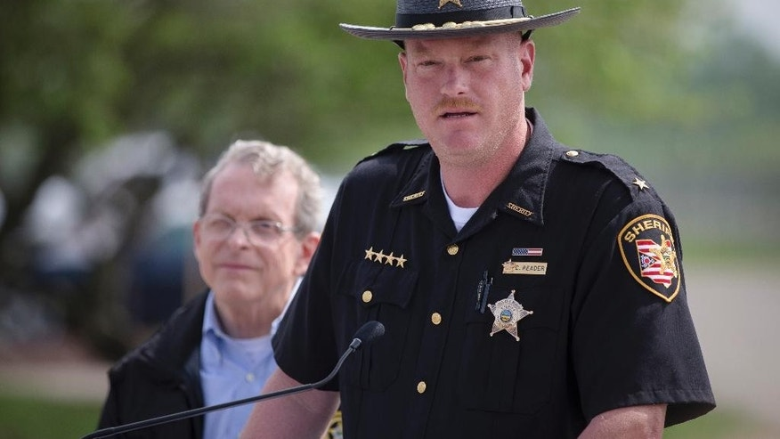 Pike County Sheriff Charles Reader speaks to the media alongside Ohio State Attorney General Mike DeWine during a news conference, Wednesday, April 27, 2016, in Waverly, Ohio. A coroner's report released Tuesday showed new details of vicious violence in the shooting deaths of eight members of a rural southern Ohio family, finding most victims were shot three to nine times each and some of them were bruised. Meanwhile, the hunt for whoever is responsible continued to expand, with more than 200 law enforcement officials involved. (AP Photo/John Minchillo)