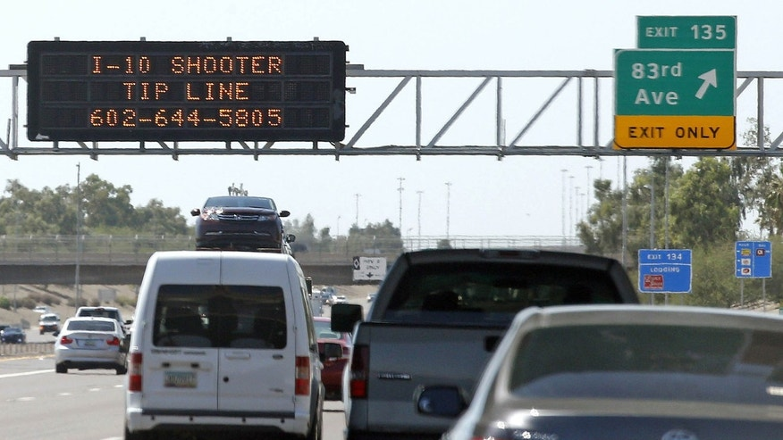 FILE - In this Sept. 11, 2015 file photo, a sign displays a shooter tip line above Interstate 10 in Phoenix.