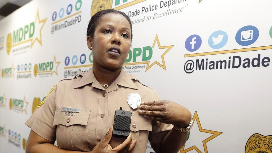 Miami-Dade Police Department PIO Marjorie Eloi shows how to turn on and off a body camera, which 1,000 officers will begin using over the next few months, during a news conference, Thursday, April 28, 2016, in Doral, Fla. Police body cameras have become more popular following a number of controversial officer shootings around the country. (AP Photo/Lynne Sladky)
