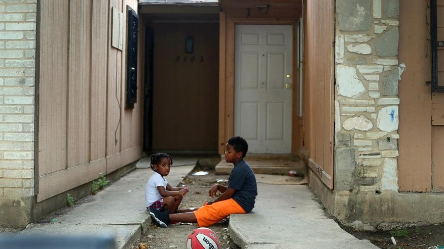 Kids play Friday April 29, 2016 in front of the townhouse at 8105 Chipping in San Antonio, Texas, where children were allegedly chained up in the back yard. Authorities say they have arrested a woman who is the mother of six of eight children who were found unsupervised in the middle of the night at a San Antonio home. A spokesman for the Bexar County sheriff's office says the 34-year-old woman also was supposed to be looking after two other children who were found tied up in the backyard. (John Davenport/The San Antonio Express-News via AP)