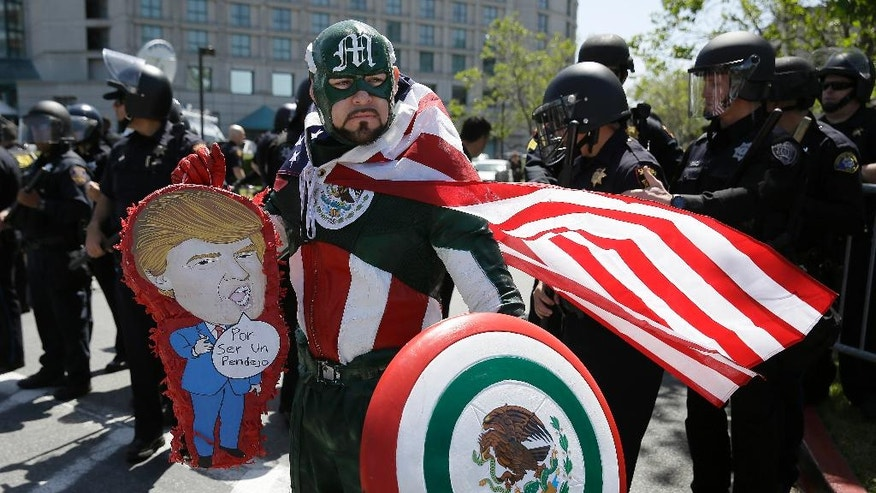 """Erik Lopez, dressed as """"Captain Mexico"""", stands in front of police officers while protesting Republican presidential candidate Donald Trump outside of the Hyatt Regency hotel during the California Republican Party 2016 Convention in Burlingame, Calif., Friday, April 29, 2016. (AP Photo/Eric Risberg)"""
