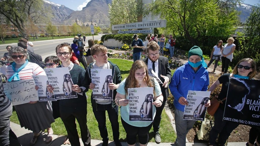 FILE - This April 20, 2016, file photo, Protesters stand in solidarity with rape victims on the campus of Brigham Young University during a sexual assault awareness demonstration, in Provo, Utah. Several Utah police officials are joining in calls to change Brigham Young University's practice of investigating students who have reported being sexually assaulted for violations of the school's strict code of behavior. (AP Photo/Rick Bowmer, File)
