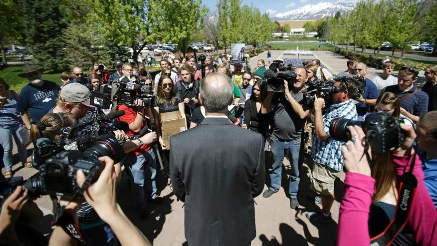 FILE - This April 20, 2016, file photo, Brent Webb Brigham Young University Academic Vice President speaks with protesters who stand in solidarity with rape victims on the campus of Brigham Young University during a sexual assault awareness demonstration, in Provo, Utah. Several Utah police officials are joining in calls to change Brigham Young University's practice of investigating students who have reported being sexually assaulted for violations of the school's strict code of behavior. (AP Photo/Rick Bowmer, File)