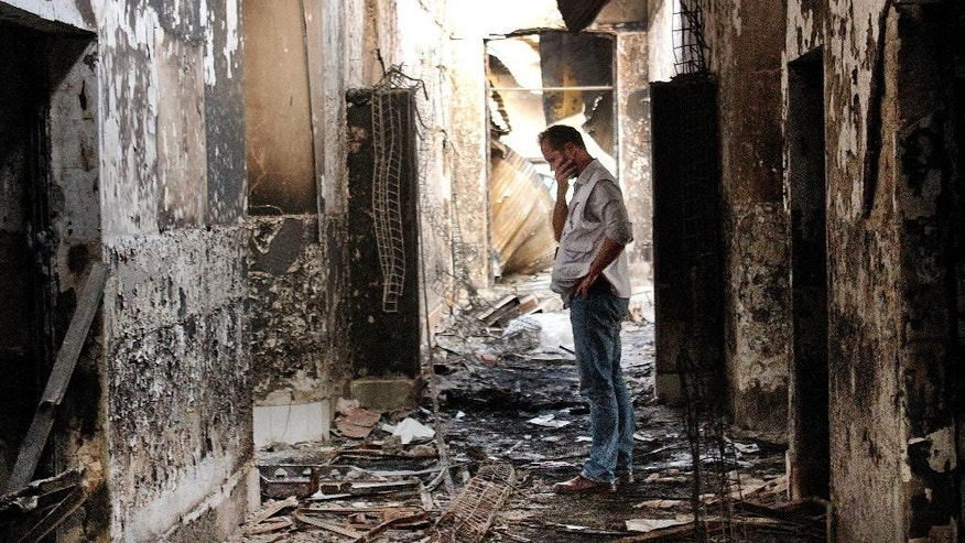 FILE - In this Oct. 16, 2015, file photo, an employee of Doctors Without Borders walks inside the charred remains of the organization's hospital after it was hit by a U.S. airstrike in Kunduz, Afghanistan. About 16 U.S. military personnel, including a two-star general, have been disciplined for mistakes that led to the bombing of the civilian hospital in Afghanistan last year that killed 42 people, a senior U.S. official said Thursday, April 28, 2016. According to officials, no criminal charges were filed and the service members received administrative punishments in connection with the U.S. air strike in the northern city of Kunduz.  (AP Photo/Najim Rahim, File)