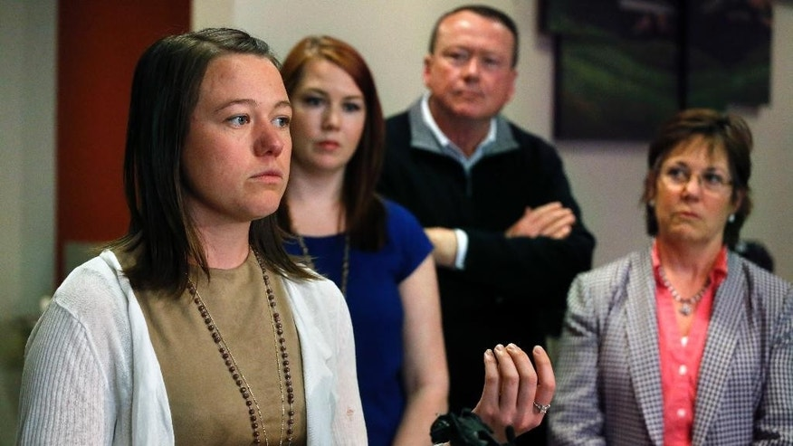 Michelle Wilkins, from left, stands with her sister Sarah, their father Mark and mother Wendy, as Wilkins speaks with members of the media following the sentencing hearing for Dynel Lane, who was given 100 years in prison for cutting the nearly 8-month-old fetus from Wilkins's womb in 2015, at the Boulder County Justice Center in Boulder, Colo., Friday, April 29, 2016. A jury convicted Lane, 36, in February, 2016 of attempting to kill Michelle Wilkins in 2015. Lane also was convicted of assault and unlawful termination of a pregnancy after luring Wilkins with an ad for maternity clothes. (AP Photo/Brennan Linsley)