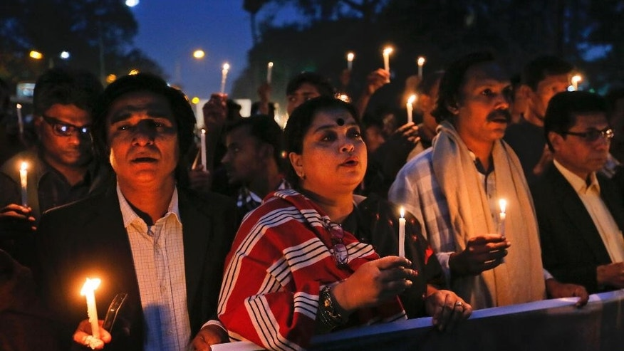 FILE - In this Dec. 14, 2015, file photo, Bangladeshi people hold lighted candles and walk in a rally during Martyrs Day in Dhaka, Bangladesh. The slaying in Bangladesh of a U.S. Agency for International Development employee has intensified U.S. concern that the strategically located South Asian country with traditions of religious tolerance is under threat from Islamic extremists. (AP Photo/A.M.Ahad)