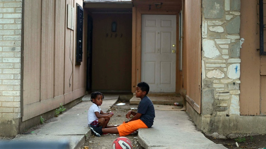 Kids play Friday April 29, 2016 in front of the townhouse at 8105 Chipping in San Antonio, Texas, where children were allegedly chained up in the back yard.