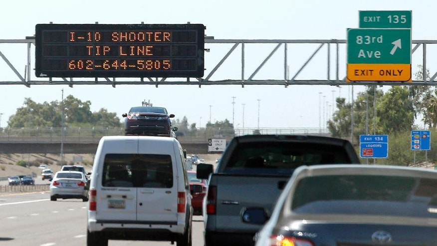 FILE - In this Sept. 11, 2015 file photo, a sign displays a shooter tip line above Interstate 10 in Phoenix. After weeks of random shootings on Phoenix freeways that rattled residents, police believed they had their man when they arrested Leslie Merritt Jr. Seven months later the entire case fell apart, leading to his release, the dismissal of charges and allegations of a botched investigation. (AP Photo/Ross D. Franklin, File)