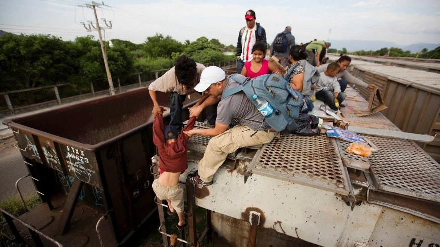 FILE  - In this Saturday, July 12, 2014 file photo, a young boy is helped down from a freight car as Central American migrants board a northbound freight train in Ixtepec, Mexico. The Rocky Mountain states have taken in less than 1 percent of the more than 100,000 unaccompanied minors who crossed the border from El Salvador, Guatemala and Honduras since the fall of 2013. The bulk — 860 — have ended up in Colorado.  (AP Photo/Eduardo Verdugo, File)