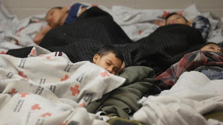 FILE - In this Wednesday, June 18, 2014 file photo, detainees sleep in a holding cell at a U.S. Customs and Border Protection processing facility in Brownsville, Texas. The Rocky Mountain states have taken in less than 1 percent of the more than 100,000 unaccompanied minors who crossed the border from El Salvador, Guatemala and Honduras since the fall of 2013. The bulk — 860 — have ended up in Colorado.  (AP Photo/Eric Gay, Pool, File)