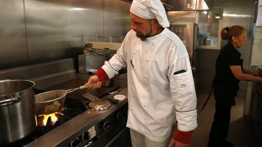 "In this photo taken April 21, 2016, nursing home food service director Chef Christopher Willard prepares meals for residents at Sunny Vista Living Center, in Colorado Springs, Colo. There's a growing trend among U.S. nursing homes to abandon rigid menus and strict meal times in favor of a more individualized approach to food. Now, the federal government is proposing regulations that would require facilities to create menus that reflect religious, cultural and ethnic needs and preferences. The rules also would empower nursing home residents with the ""right to make personal dietary choices."" (AP Photo/Brennan Linsley)"
