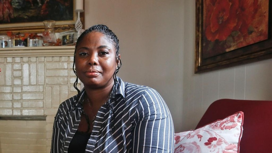 FILE- In this Nov. 12, 2015, file photo, Gwendolyn Smalls poses for a photo in her home in Richmond, Va. Smalls' brother, Linwood R. Lambert Jr., died in police custody in May of 2013 after being repeatedly stunned by South Boston police. Smalls and her attorney told The Associated Press on Monday, May 2, 2016, that Halifax County Commonwealth's Attorney Tracy Quackenbush Martin said she doesn't believe there's enough evidence to bring criminal charges against South Boston Police Officers Tiffany Bratton, Clifton Mann and Travis Clay. (AP Photo/Steve Helber, File)