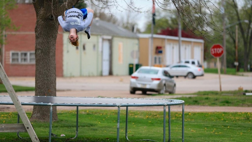 Taylor Ladd does a back flip on the trampoline with the fire hall seen in the background in Nickerson.