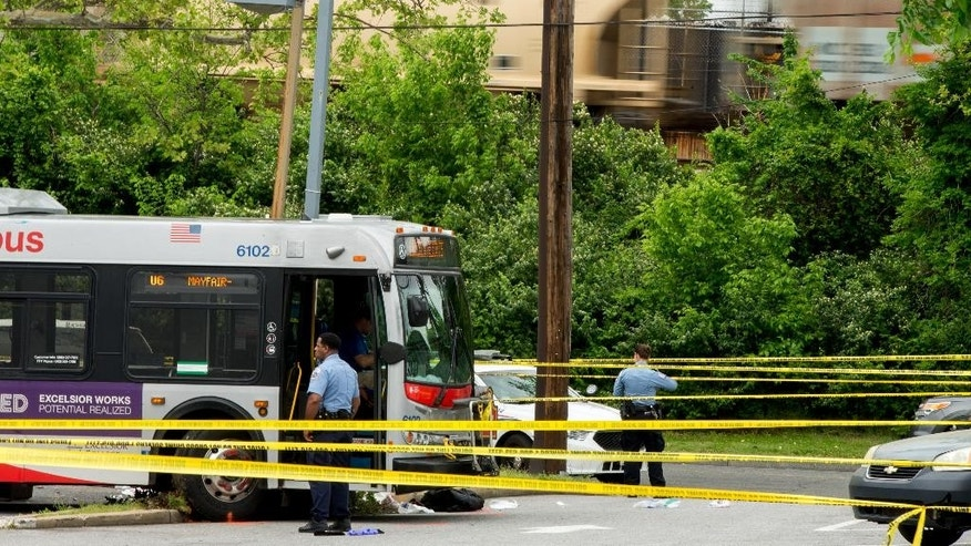 Police work a crime scene after authorities say a man attacked a bus driver, stole the bus, then struck and killed a man after the bus jumped a curb at a gas station at the corner of Helen Burroughs Avenue and Minnesota Avenue in Northwest Washington, Tuesday, May 3, 2016. (AP Photo/Andrew Harnik)
