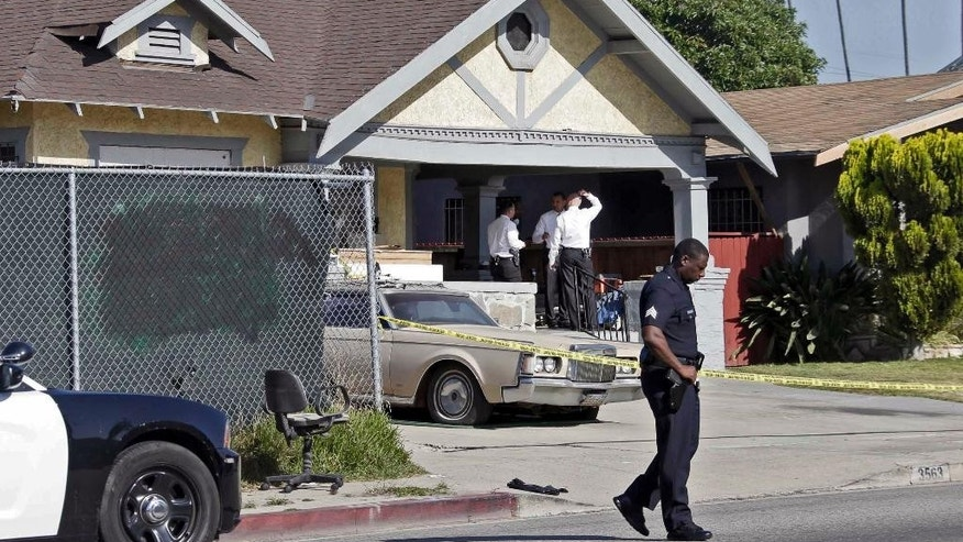 Los Angeles police investigate a stabbing at a house in Los Angeles on Tuesday, May 3, 2016. Donald Gray is suspected of stabbing his live-in girlfriend and her 2-year-old daughter in their home, killing the little girl and critically wounding her mother, who was five months pregnant, authorities said. (AP Photo/Nick Ut)