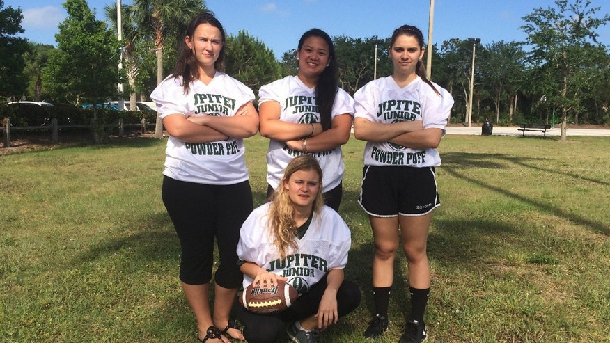 In this photo taken Monday, May 2, 2016, Jupiter High powderpuff football players Caitlin Walsh, Megan Mendoza, Haley Osborne and Savannah Tardonia, in front with ball, pose for a group photo in Jupiter, Fla.