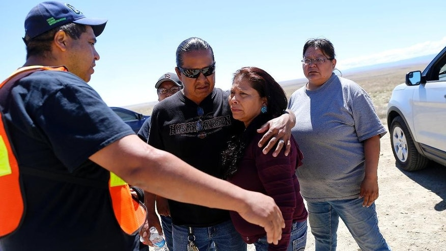 Family and friends gather along Navajo Route 13 south of Shiprock, N.M., Tuesday, May 3, 2016, just a few miles from where Ashlynne Mike's body was discovered. Authorities are poring over parts of the Navajo Nation in search of the man who snatched Ian and Ashlynne Mike and killed Ashlynne. Tips are flooding in from across the reservation that spans parts of New Mexico, Arizona and Utah as well as the close-knit tribal community where Ashlynne lived.  (Jon Austria/The Daily Times via AP) MANDATORY CREDIT