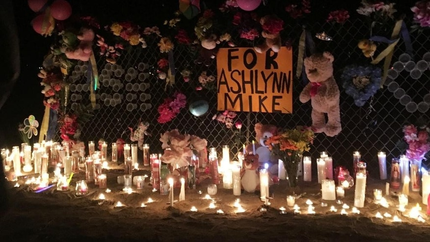 In this May 3, 2016 photo, candles burn at a makeshift memorial for Ashlynne Mike on the Navajo Nation southwest of Farmington, N.M. The FBI said Mike, was abducted after school on Monday, May 2, and her body was found the next day. (AP Photo/Mary Hudetz)
