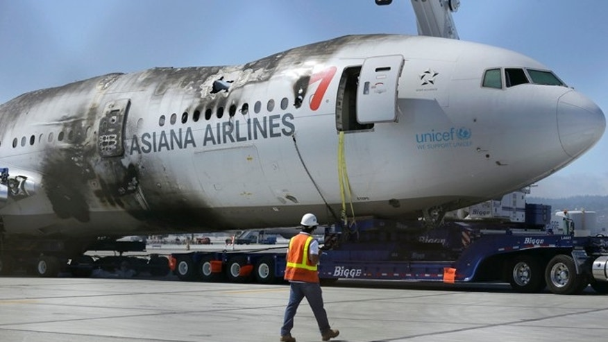 JULY 2013 FILE: A man walks past the wreckage of Asiana Flight 214 at San Francisco International Airport.