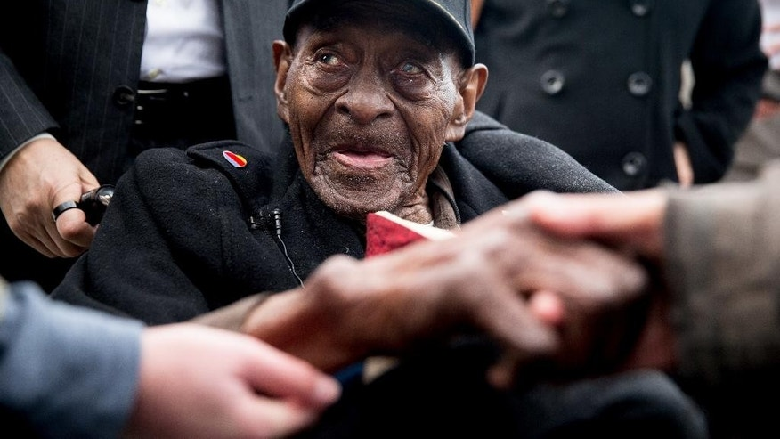 FILE - In this Dec. 7, 2015 file photo, Frank Levingston Jr., of Lake Charles, La.,  is greeted by visitors following a wreath laying ceremony to mark the anniversary of Pearl Harbor at the World War II Memorial in Washington.  Levingston, a 110-year-old veteran who served in World War II has died, on Tuesday, May 3, 2016.  (AP Photo/Andrew Harnik)