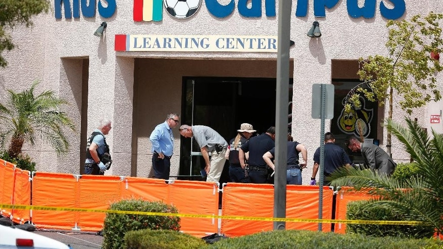 North Las Vegas authorities investigate the scene of a fatal shooting at a daycare Thursday, May 5, 2016, in North Las Vegas, Nev. Authorities say a domestic-related shooting in front of the suburban Las Vegas day care center left a man and woman dead and two young children hospitalized with gunshot wounds.  (AP Photo/John Locher)