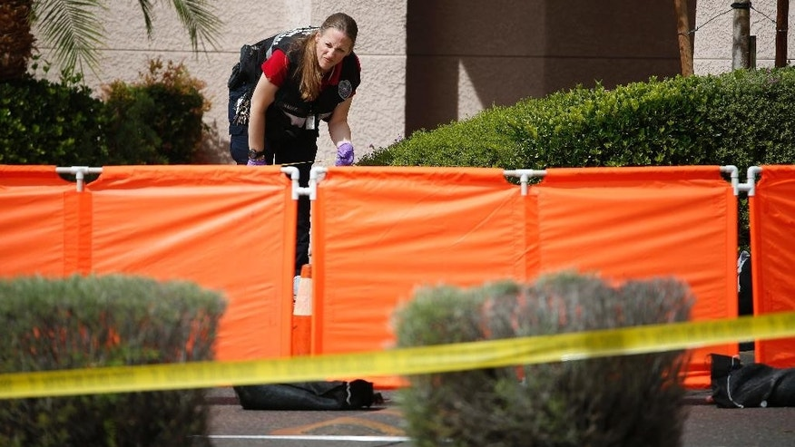 North Las Vegas authorities investigate the scene of a fatal shooting Thursday, May 5, 2016, in North Las Vegas, Nev. Authorities say a domestic-related shooting in front of the suburban Las Vegas daycare left a man and woman dead and two young children hospitalized. (AP Photo/John Locher)