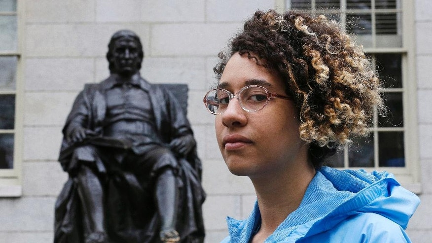 Brianna Suslovic poses at the foot of the John Harvard statue in Harvard Yard prior to presenting a study concerning the history of oppression at Harvard University in Cambridge, Mass., Thursday, May 5, 2016. A group of Harvard students delivered lessons as part of a new research project meant to cast light on the darker corners of the university's past, and to lift up figures that history has long overlooked. (AP Photo/Charles Krupa)