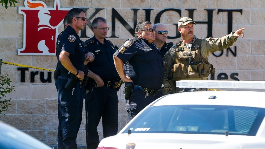 Sheriff's deputies surround Knight Transportation after a recently dismissed man opened fire inside the facility, fatally shooting a former co-worker before turning the gun on himself, Wednesday, May 4, 2016, in Katy, Texas.