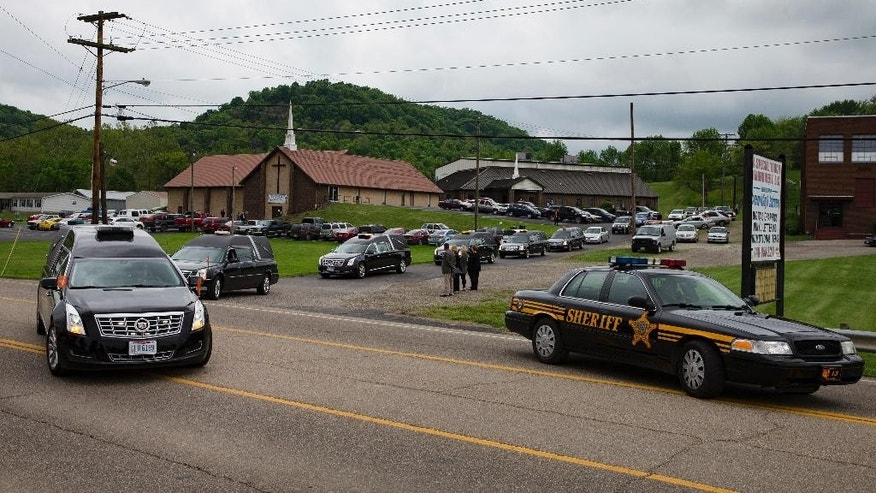 Six hearses depart from Dry Run Church of Christ during funeral services for six of the eight murder victims from Pike County, Tuesday, May 3, 2016, in West Portsmouth, Ohio. Seven adults and a 16-year-old boy from the Rhoden family were found dead April 22 at four properties scattered across a few miles of countryside near Piketon, about 80 miles east of Cincinnati.   (AP Photo/John Minchillo)