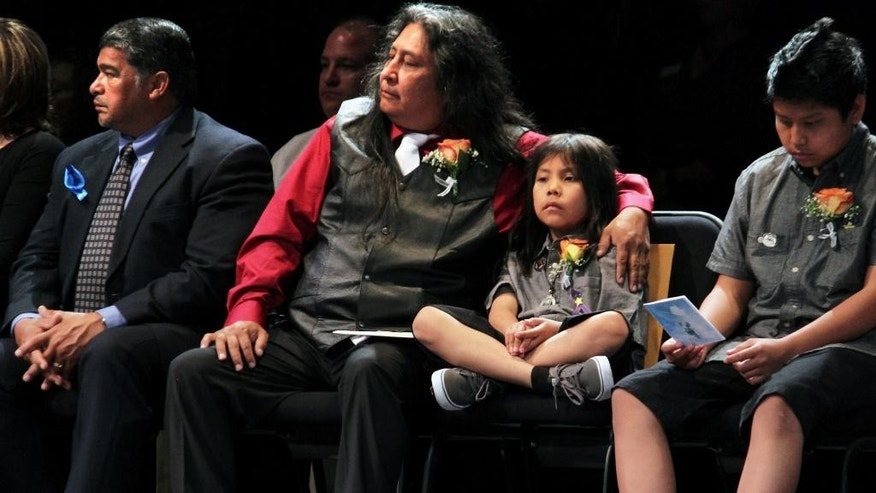Gary Mike, center, has his arm around his 9-year-old son Ian as they listen to fellow family members speak about his 11-year-old daughter Ashlynne Mike during her public memorial service in Farmington, N.M., on Friday, May 6, 2016. The girl was killed after being abducted from the Navajo Nation as she and her brother played after school. (AP Photo/Susan Montoya Bryan)