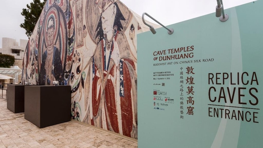 "In this Wednesday, May 4, 2016, photo, in an exhibition curators say is unprecedented, three full-scale, hand-painted replica caves have been erected on The Getty museum's hilltop campus. The exhibit ""Cave Temples of Dunhuang: Buddhist Art on the Silk Road"" opens Saturday, May 7, and runs until Sept. 4, 2016 at the Getty Center. (AP Photo/Damian Dovarganes)"